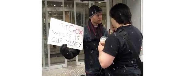 """Ai primi di febbraio, un australiano è volato fino a Tokio per protestare contro la scarsa trasparenza a suo dire di MTGOX. Con un cartello con recante la scritta """"dove sono i nostri Bitcoin?"""" si è parato davanti a Mark Karpeles, il 28enne CEO della piattaforma (di spalle nella foto). Tutta la vicenda è poi stata raccontata su Reddit."""