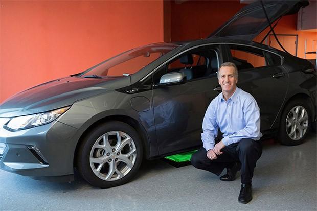 Alex Gruzen, CEO di WiTricity, con una Chevrolet Volt parcheggiata sopra al sistema per la ricarica wireless della batteria